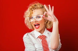 Smiling stylish woman showing sign excellently, isolated on red