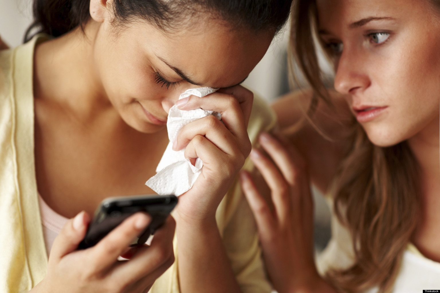 women-crying-together-cell-phone