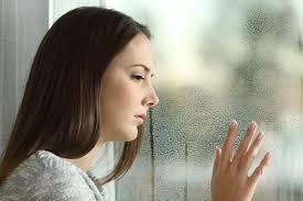 wistful woman looking out wet window